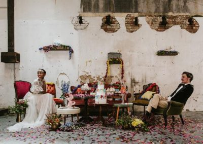 bride and groom sitting in colourful lounge setup