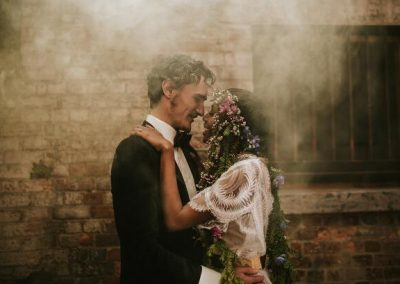 bride and groom about to share a kiss in a smokey laneway