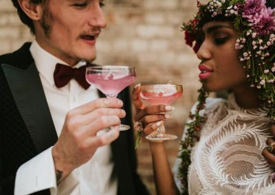 bride and groom cheersing with cocktails