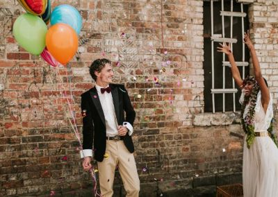 bride happily throwing confetti at groom