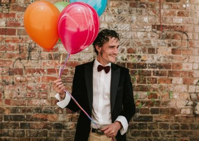 groom smiling while holding colourful balloons