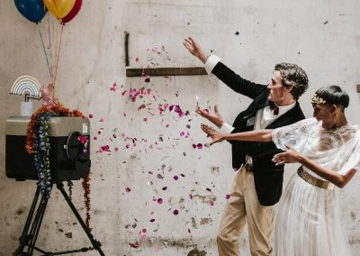 couple throwing confetti at camera