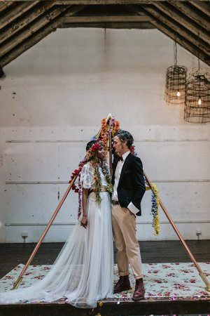 bride and groom in front of tipi arch