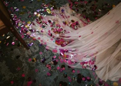 pink confetti on white wedding dress