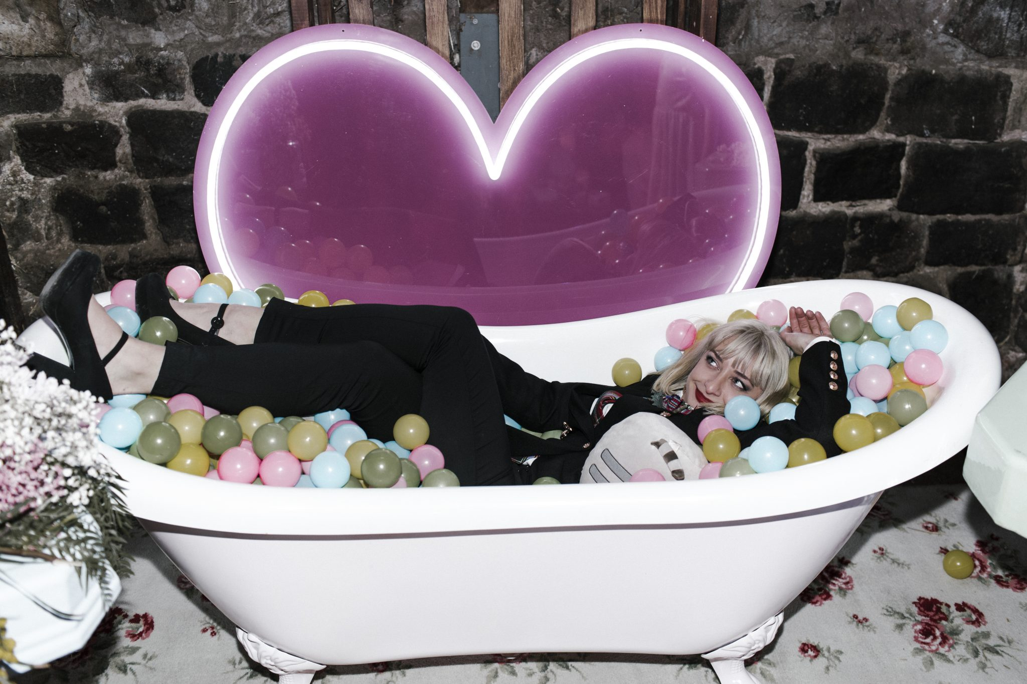 Pink bathtub ball pit and giant heart neon sign