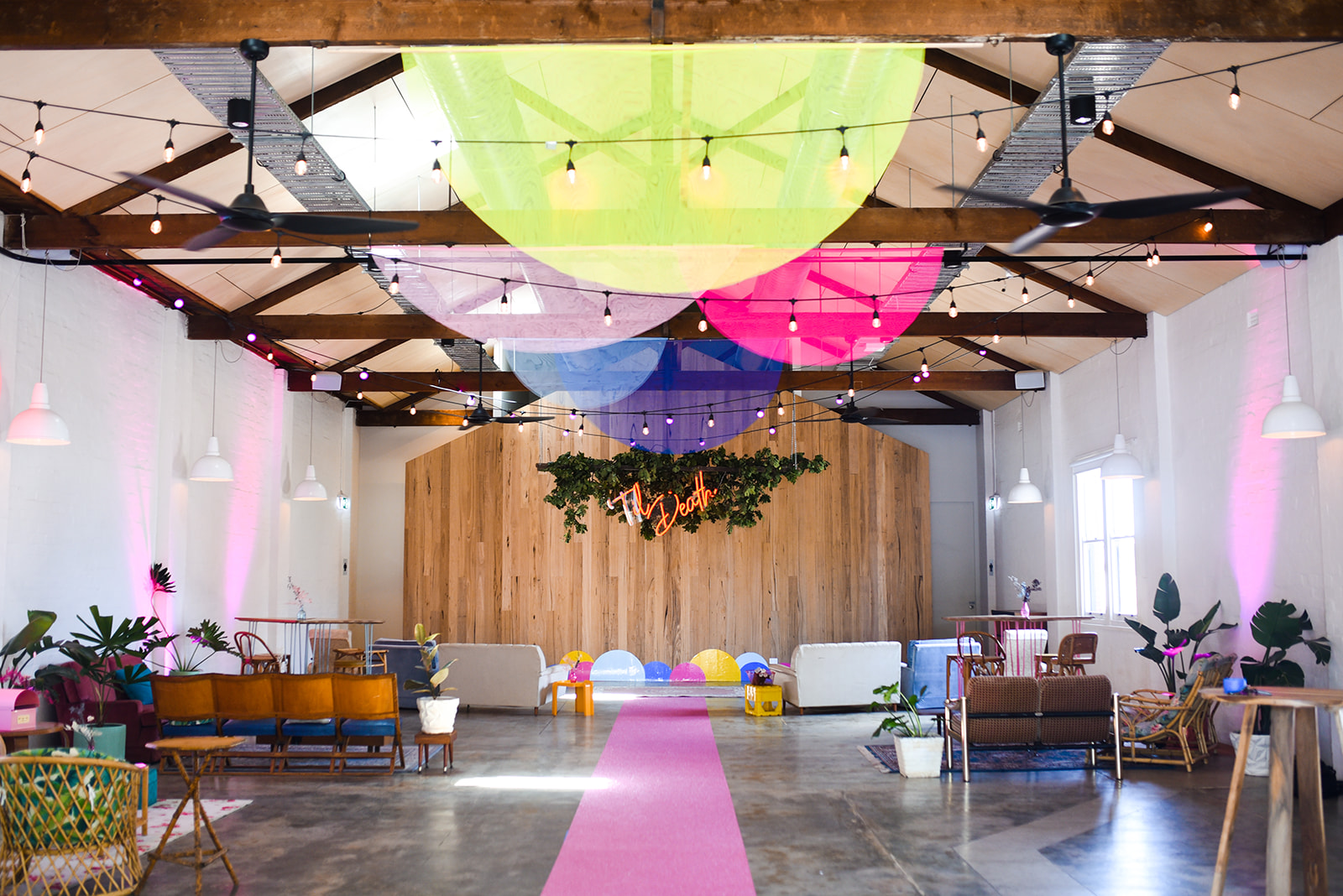 wooden backdrop with til death neon sign and greenery hanging over head for ceremony