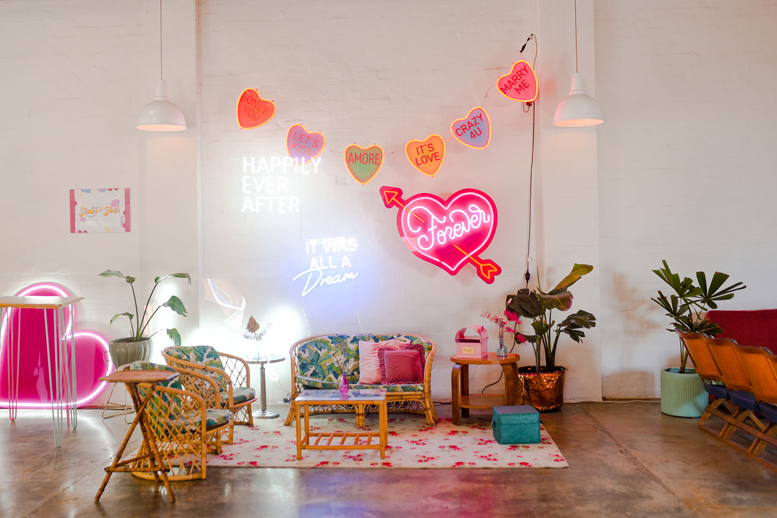 Neon signs and lights hanging on white wall as a backdrop to eclectic vintage lounge area
